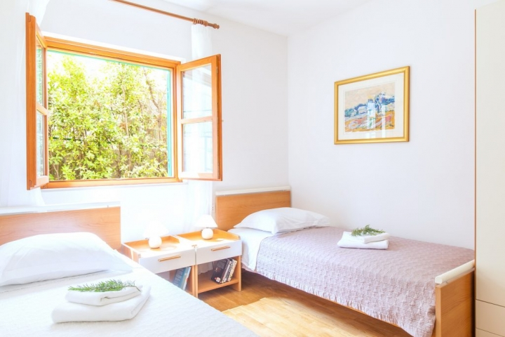 Twin bedded room with window and a garden view