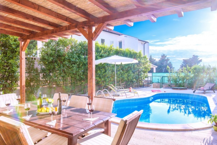 Covered outside dining table with the view on swimming pool and bed chairs with parasol
