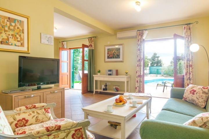 Living room with open French doors and swimming pool view